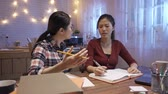 two young angry asian girl students sitting in dark home kitchen while writing notes and quarrel. group of chinese female teamwork partners women mad and discussion on project at late night.