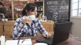 serveuse : millennial asian female student searching online information on laptop computer in cafe preparing for test. young woman studying and drinking hot tea in coffee house. college girl typing on keyboard.