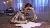 debts : worried young single japanese mother feeling stressed while working through finances in kitchen late at night. woman thinking how to pay off debts for rent and domestic bills. Financial problem