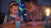 lehre : mother teaches her daughter to make a Christmas toy.