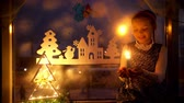 сочельник : little girl looks candle and dreams. New Year decorations Christmas tree. Стоковые видеозаписи