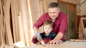 kézműves : family, carpentry, woodwork and people concept. father teaches son carpentry.