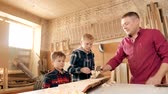 family, carpentry, woodwork and people concept. father teaches son carpentry.