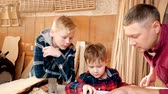 schreiner : family, carpentry, woodwork and people concept. father teaches son carpentry.
