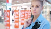sleva : Concept of a woman with a bank card is thinking about buying in a mall. A sign of the sale in the store. Dostupné videozáznamy