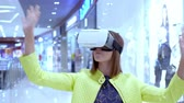 zeki : little child girl playing game in virtual reality glasses in the mall. Stok Video