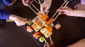 rohlíky : A set of sushi rolls on a table in a restaurant. A party of friends eating sushi rolls using bamboo sticks.