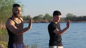 postura : The performance of Wing Chun by strong men near river. Slowly Stock Footage