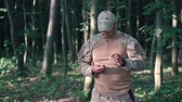 valente : Military sharpen knife with bilestone in the forest Stock Footage