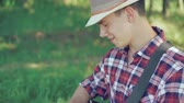 best : Portrait of guitarist in hat playing the guitar in sunny green park. 4k