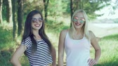 bordo : Two pretty girls with claret lips posing to camera in the park. 4k