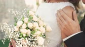 elegance : Wedding bouquet in brides hands. Groom touching bride. 4K Stock Footage