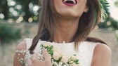 bordo : Happy bride embracing bouquet and looking aside. Slowly Stok Video