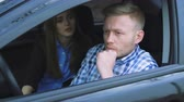 coming in : Unhappy man arguing in car, while woman calms him in 4K