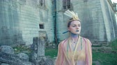 personage : The girl in the image of peahen posing near the ancient castle 4K