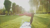 шпагат : Young girl training gymnastics in the park among the sun glare 4K