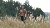 kickboxer : Free fighter walks with pungent peg in a wild field. Slowly Stock Footage
