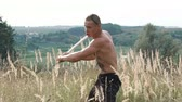 kickboxer : Free fighter training with pungent peg in wild field. Slowly