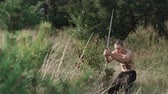 steppe : Free fighter training with swords in wild field. Slowly