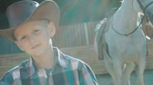 przyjaźń : Portrait of stylish little cowboy stands near purebred horse on sunlight. Slowly