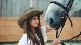 caressing : Young happy girl caressing her pretty white horse on the area. 4K Stock Footage
