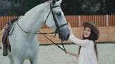 caressing : Young happy girl smiling and caressing her pretty white horse on the area. 4K