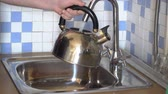 faucet : A man pours water into a kettle from a tap