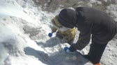 rýč : CHAPAEVSK, SAMARA REGION, RUSSIA - MARCH 15, 2018: A small child is playing with snow. Childrens shovel, scoop and molds. Mother is nearby Dostupné videozáznamy