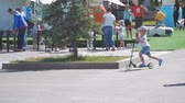 precipitação : SAMARA, RUSSIA - JUNE 21, 2018: A little girl in shorts riding a scooter in the Park. Slow motion Stock Footage