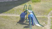 home improvement : Russia, Samara, August 01, 2018: Workers paint a childrens slide on the Playground Stock Footage