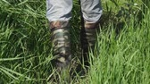 pés : A man walks along the thick grass in khaki boots of protective color