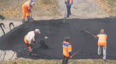 paver : CHAPAEVSK, SAMARA REGION, RUSSIA - OCTOBER 17, 2018: Road street repairing works. Construction workers during asphalting road. Manual labor in construction Stock Footage