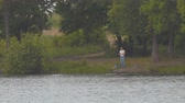decoy : Fisherman on the opposite shore of the lake with a fishing rod. Long shot