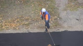 obnova : Road street repairing works. Female worker during asphalting road. Heavy female manual labor in construction Dostupné videozáznamy