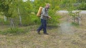 предотвращать : Pest Control. The man sprays the grass against insect pests. Spraying of insecticides at lawn Стоковые видеозаписи
