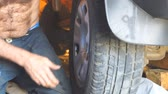 механик : Repair wheels in the garage. Man replaces the wheel