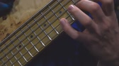 rock'çı : The bass player plays on a five-string bass guitar close-up. Plays bass guitar. Selective focus Stok Video