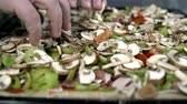 leeks : Close shot of rearranging the vegetables around the pizza in slow motion Stock Footage