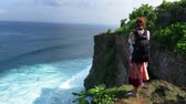indonesia : Woman standing on cliffs edge in Uluwatu and taking photos Stock Footage