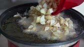 hranolky : Putting potatoe in hot oil to warm it up. Person is putting fried potato in hot sunflower oil just to warm it up and to be crunchy