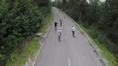 cornering : Group of longboard skaters driving on forest road aerial footage. Slow motion shot of group of people on skateboard riding down the woods road.