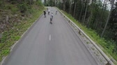 cornering : Tracking group of longboarders in slow motion. Wide shot flying behind group of skaters on longboard driving through forest of spruce. Stock Footage
