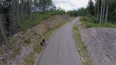 cornering : Aerial wide shot of wide asphalt road and longboarder riding. Dangerous longboard descent on road through forest with two viewers beside.