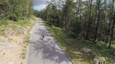 cornering : Fast longboard skaters dowhnill. Aerial footage of extreme sport riding on fast longboard skate for downhill roads in slow motion.