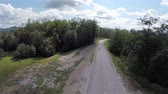 cornering : Aerial shot of road and forest while skaters drives through. High in air landscape shot of tall spruce forest with empty road travel through.