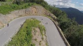 cornering : Longboard skaters speeding downhill one after another. Aerial footage slow motion of competitors riding on empty forest roads downhill on special skateboard longboard.