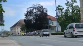 j��zda na kole : VRHNIKA, SLOVENIA - JUNE 2014: Support cars following bicycle group in city. Wide shot of some group of cyclists followed by support vehicles.