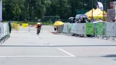 j��zda na kole : VRHNIKA, SLOVENIA - JUNE 2014: Biker stopping after finish line. Medium shot of finish line for bicycle competition, competitor driving through and slowly stopping.