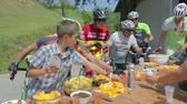 j��zda na kole : VRHNIKA, SLOVENIA - JUNE 2014: Bicycle competitors taking a break eat lunch. Break stop for a snack and drink after long travel in bicycle competition on a sunny day.