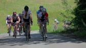 j��zda na kole : VRHNIKA, SLOVENIA - JUNE 2014: Cyclists pushing hard uphill in bicycle competition. Driving in front of cycling group going uphill in a race on a sunny weather. Dostupné videozáznamy